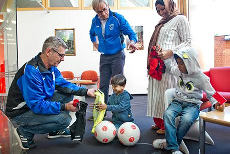 Geschenke zur Kontoeröffnung in der SSK: Die Vorstandsmitglieder Erk Bratke (links) und Heinz-Werner Gottlob (stehend) rüsteten Flüchtlingskinder mit Fußballutensilien aus.