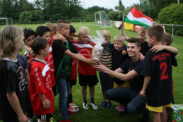Verabschiedung: Die Kinder der AGS-Fußball-AG überreichten ihrem scheidenden Trainer Marvin Marten einen Pokal als Dankeschön. Foto: Bratke