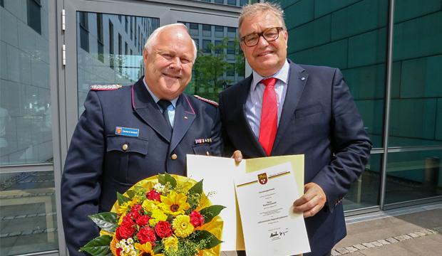Mit Nadel, Urkunde und Blumen: Regionspräsident Hauke Jagau (r.) gratuliert Eberhard Schmidt zur Ernennung als stellvertretender Regionsbrandmeister. Foto: Region Hannover